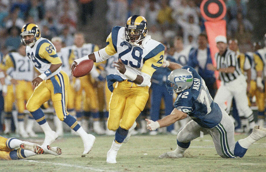 FILE - In this Aug. 13, 1987, file photo, Los Angeles Rams running back Eric Dickerson (29) breaks away as Seattle Seahawks nose tackle Joe Nash misses the tackle during the first quarter of an NFL preseason football game in Anaheim. Eric Dickerson is thrilled his Rams have returned to Los Angeles after 21 years away, but the Hall of Fame running back says the current players in the horned helmets must be ready for both the challenges and the opportunities presented by playing in the nation's glitzy entertainment capital. (AP Photo/Lennox McLendon, File)