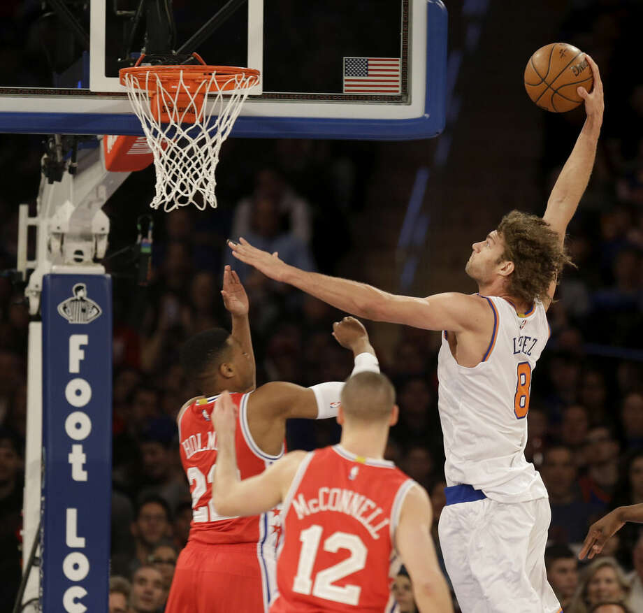 New York Knicks' Robin Lopez, right, dunks over Philadelphia 76ers' defenders during the first half of an NBA basketball game, Monday, Jan. 18, 2016 in New York. (AP Photo/Seth Wenig)