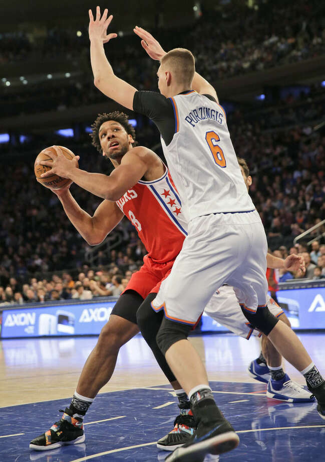 Philadelphia 76ers' Jahlil Okafor, left, looks for a shot past New York Knicks' Kristaps Porzingis during the first half of an NBA basketball game, Monday, Jan. 18, 2016 in New York. (AP Photo/Seth Wenig)