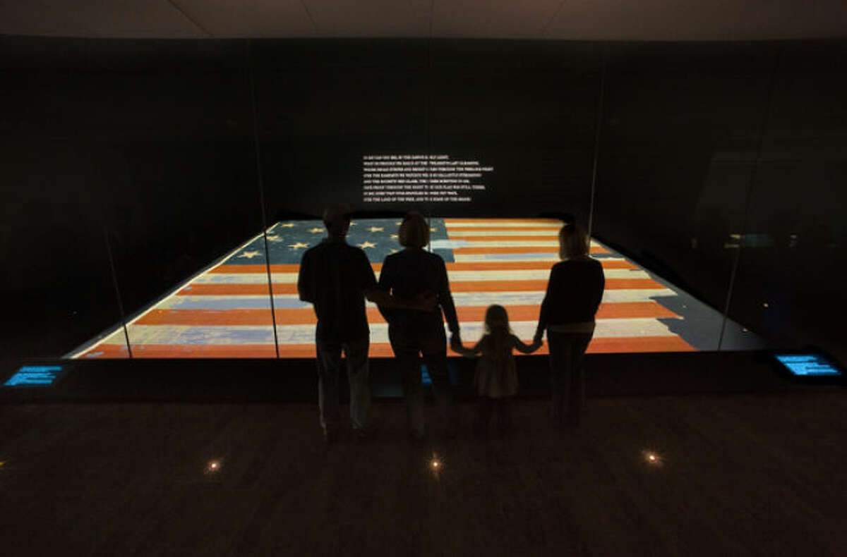 """This handout photo provided by the Smithsonian Institution, taken in Nov. 2008, shows a family viewing the Star Spangled Banner at the Smithsonian's National Museum of American History in Washington. The original, handwritten manuscript of ?""""The Star-Spangled Banner?"""" and the flag that inspired the song?'s lyrics will be displayed together at the Smithsonian in Washington, what is believed to be the first time the historic pieces have been shown side-by-side, on Flag Day, June 14, through July 6. (AP Photo/Hugh Talman, Smithsonian Institution)"""