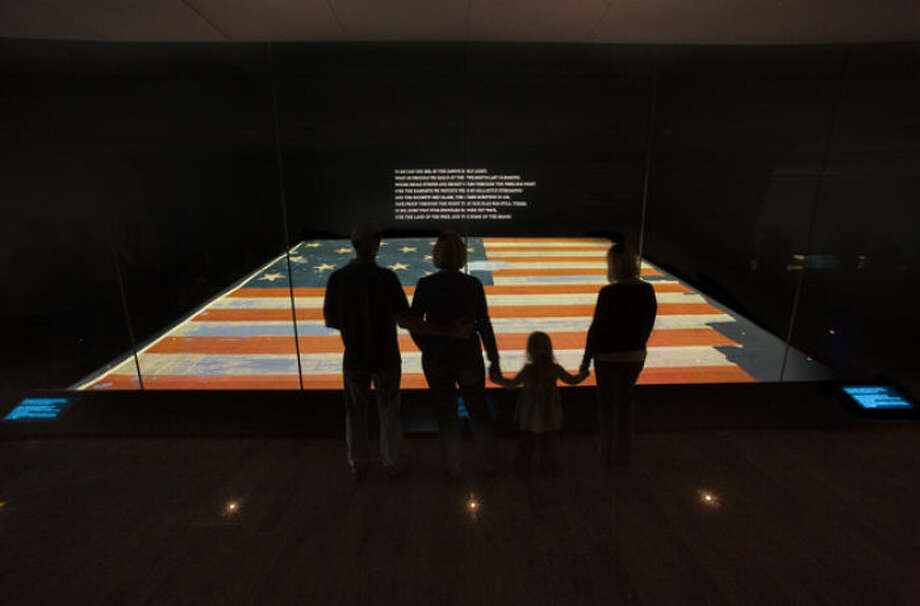 "This handout photo provided by the Smithsonian Institution, taken in Nov. 2008, shows a family viewing the Star Spangled Banner at the Smithsonian's National Museum of American History in Washington. The original, handwritten manuscript of ""The Star-Spangled Banner"" and the flag that inspired the song's lyrics will be displayed together at the Smithsonian in Washington, what is believed to be the first time the historic pieces have been shown side-by-side, on Flag Day, June 14, through July 6. (AP Photo/Hugh Talman, Smithsonian Institution)"