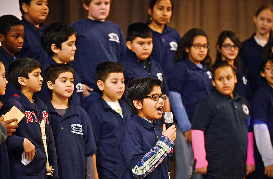 Hour photo / Erik Trautmann Jefferson Science Magnet School 5th grader Shameel Aubeelauch sings a solo in Follow Me to the Top with the choir as they celebrate the National Blue Ribbon Award the school received for closing the achievement gap between student su-groups during a ceremony Tuesday morning.