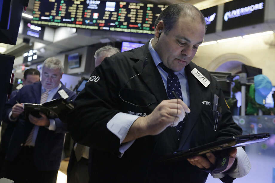 Trader Anthony Riccio, right, works on the floor of the New York Stock Exchange, Tuesday, Jan. 19, 2016. U.S. stocks are opening higher, led by gains in banks and technology companies. (AP Photo/Richard Drew)