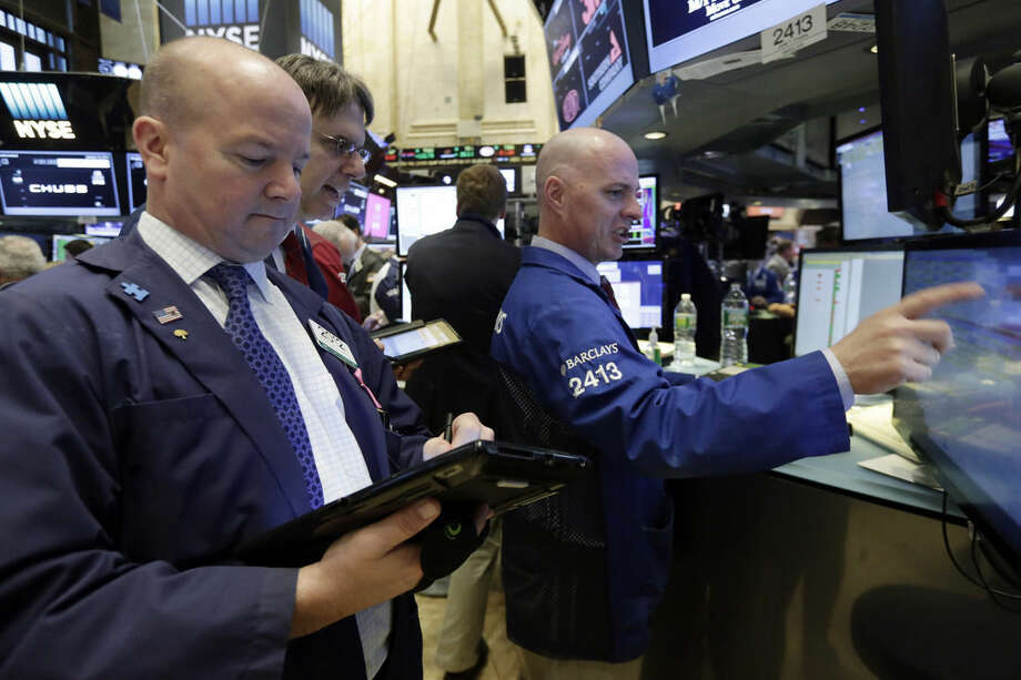 Specialist John O'Hara, right, works with traders on the floor of the New York Stock Exchange, Tuesday, Jan. 19, 2016. U.S. stocks are opening higher, led by gains in banks and technology companies. (AP Photo/Richard Drew)