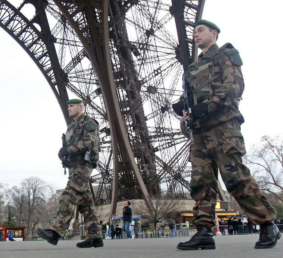 French army soldiers patrol under the Eiffel Tower in Paris, Tuesday Jan. 13, 2015. France on Monday ordered 10,000 troops into the streets to protect sensitive sites after three days of bloodshed and terror, amid the hunt for accomplices to the attacks that left 17 people and the three gunmen dead. (AP Photo/Remy de la Mauviniere)