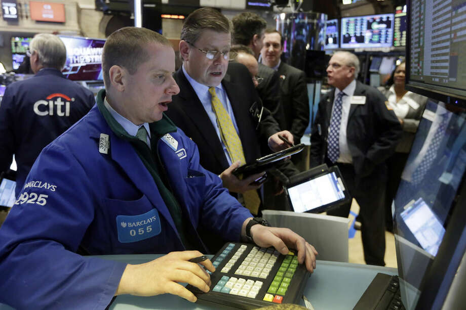 Specialist Robert Nelson, left, works at his post on the floor of the New York Stock Exchange, Tuesday, Jan. 19, 2016. U.S. stocks are opening higher, led by gains in banks and technology companies. (AP Photo/Richard Drew)