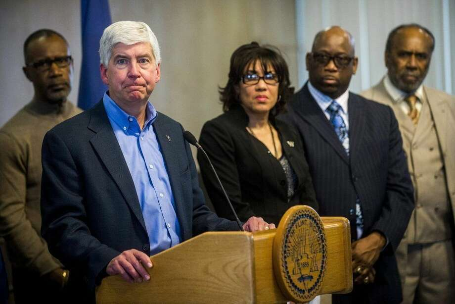 FILE - In a Monday, Jan. 11, 2016 file photo, Michigan Gov. Rick Snyder speaks during a news conference in Flint, Mich. the fallout from a water crisis in another impoverished city have marred the Republican's image as a practical problem-solver.Snyder is preparing to deliver his sixth State of the State address Tuesday, Jan. 19, where he will be met by a large protest that is likely to echo the withering criticism over Flint's water disaster coming from inside and outside of Michigan. (Jake May/The Flint Journal-MLive.com via AP, File) LOCAL TELEVISION OUT; LOCAL INTERNET OUT; MANDATORY CREDIT