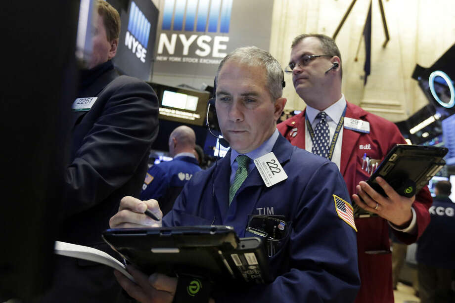 Trader Timothy Nick, center, works on the floor of the New York Stock Exchange, Tuesday, Jan. 19, 2016. U.S. stocks are opening higher, led by gains in banks and technology companies. (AP Photo/Richard Drew)