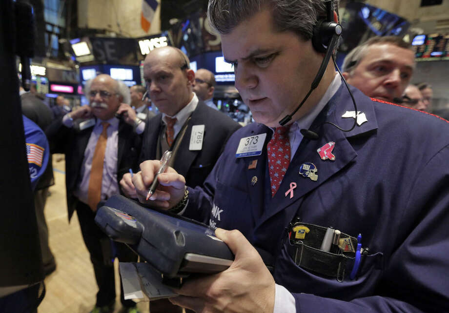 John Panin, foreground right, works with fellow traders on the floor of the New York Stock Exchange Monday, Jan. 12, 2015. Stocks are moving lower in early trading, led by a decline in energy stocks as the price of oil falls again. (AP Photo/Richard Drew)