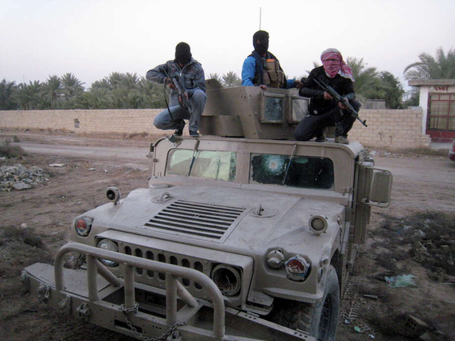 Gunmen sit on top of an Iraqi army Humvee, left by Iraqi soldiers during clashes in Fallujah, 40 miles (65 kilometers) west of Baghdad, Iraq, Thursday, Jan. 9, 2014. Tribal leaders in Fallujah have warned al-Qaida fighters there to leave to avoid a military showdown, and there were signs that residents of Fallujah were trying to restore a sense of normalcy, however precarious. (AP Photo) / AP