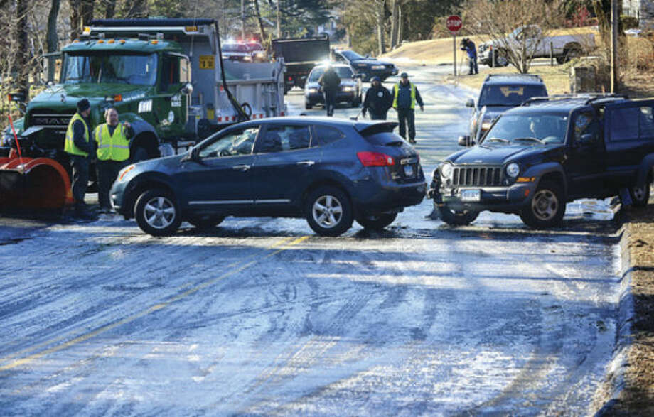 Hour photo / Erik TrautmannA pool water drained from a residence on Westview Lane ice over a treacherous curve on Flax Hill Road causing a multi-vehicle accident that including a DPW plow who was addressing the icing issue Thursday morning.