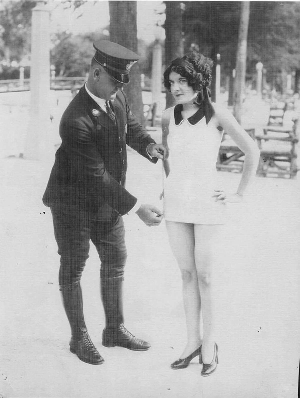 The '20s: A San Antonio Police Department captain measures the swimsuit of a young woman, believed to be Miss San Antonio 1927 Florence Zoeller at San Pedro Park.
