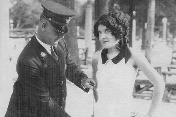 The San Antonio Police Department Historical Society shared a rare photo of a SAPD official measuring the swimsuit of a young woman, believed to be Miss San Antonio 1927 Florence Zoeller, sometime between 1925 and 1929.