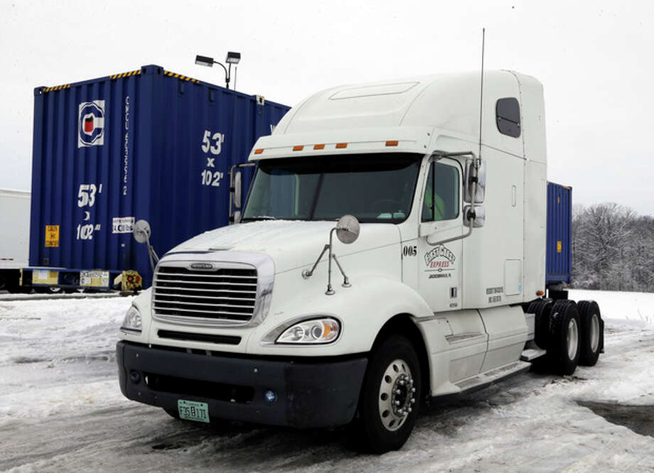 The tractor trailer where Tim Rutledge, 53, of Orlando, Fla., says he crawled under before dawn Monday to fix its frozen brakes when it suddenly settled deeper into the snow, pinning him beneath an axle remains at a truck stop just in Whiteland, Ind., Thursday, Jan. 9, 2014. (AP Photo/Michael Conroy) / AP