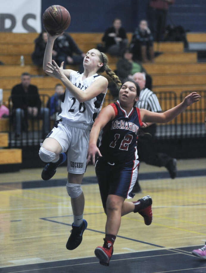 Hour photo/John Nash - Staples' Tessa Mall, left, moves in a lay up as Brien McMahon's Kyle Courtney arrives a little too late to stop her during Thursday's game in Westport.