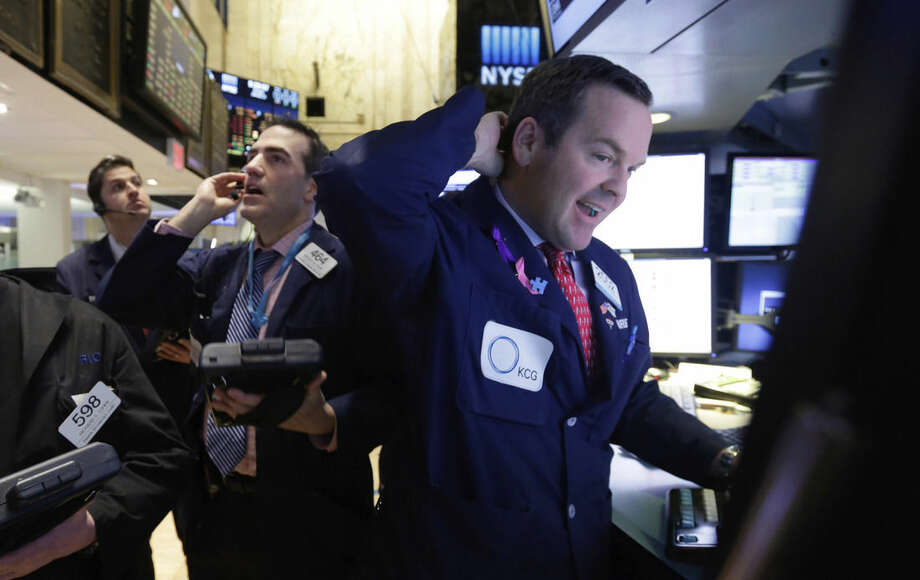 Specialist Charles Boeddinghaus, right, works with traders on the floor of the New York Stock Exchange Monday, Jan. 12, 2015. Stocks are moving lower in early trading, led by a decline in energy stocks as the price of oil falls again. (AP Photo/Richard Drew)