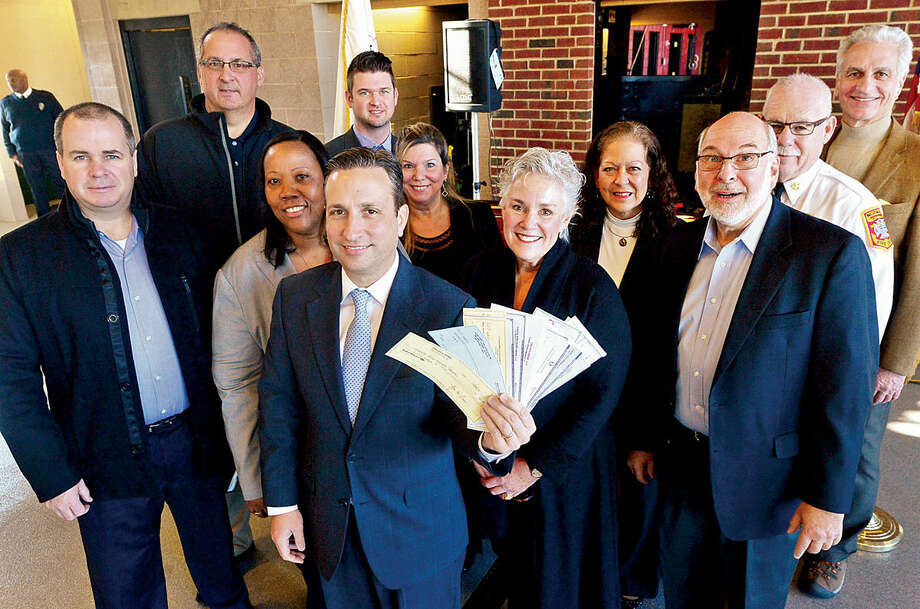 Hour photo / Erik Trautmann MattHefferan of Norwalk PAL, Rob Roveta of Safelie Autoglass, Novelette Peterkin of Carver Foundation, John Hurt of Companions and Homemakers, Jane Morell of Aetna, Ceci Maher of Person-to-Person, Lorna Sura from Norwalk PAL, Stephen Bentkover from Norwalk Reads, Norwalk Fire Chief Laryy Reilly and Paul Cianelli of New England Cable and Telecommunications Association join State Senator and Majority Leader, Bob Duff (D-25), center, as he holds a press conference Thursday morning at the Norwalk Fire Department to present checks to various organizations from his annual fundraising effort, The Duff's Community Holiday Open House.