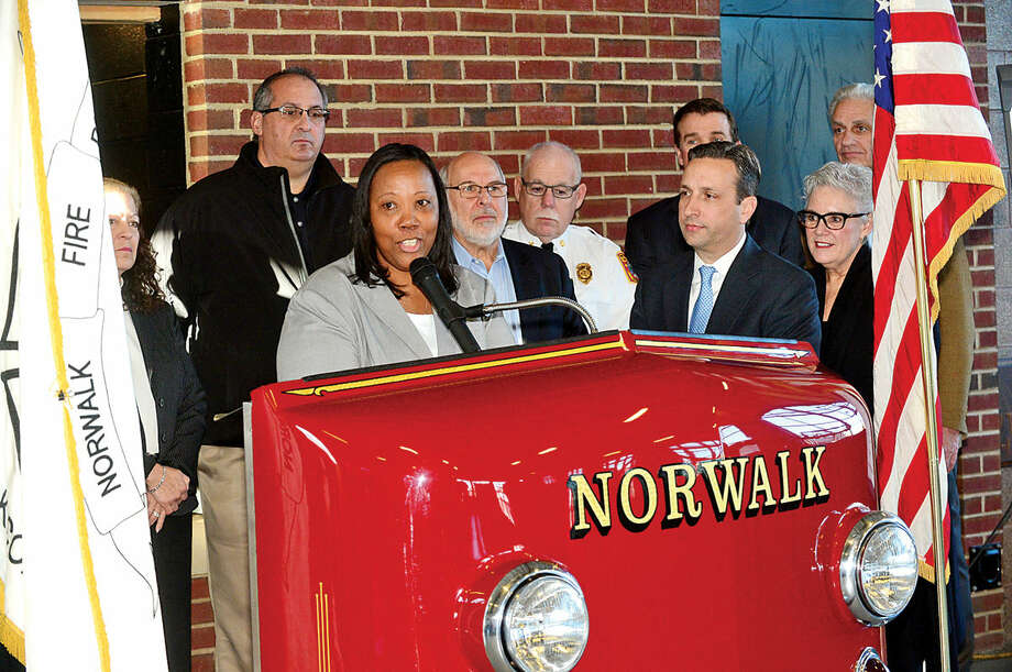 Hour photo / Erik Trautmann Carver Foundation Executive Director, Novelette Peterkin, speaks as State Senator and Majority Leader, Bob Duff (D-25), holds a press conference Thursday morning at the Norwalk Fire Department to present checks to various organizations from his annual fundraising effort, The Duff's Community Holiday Open House.
