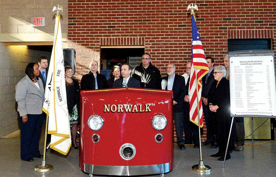 Hour photo / Erik Trautmann State Senator and Majority Leader, Bob Duff (D-25), holds a press conference Thursday morning at the Norwalk Fire Department to present checks to various organizations from his annual fundraising effort, The Duff's Community Holiday Open House.