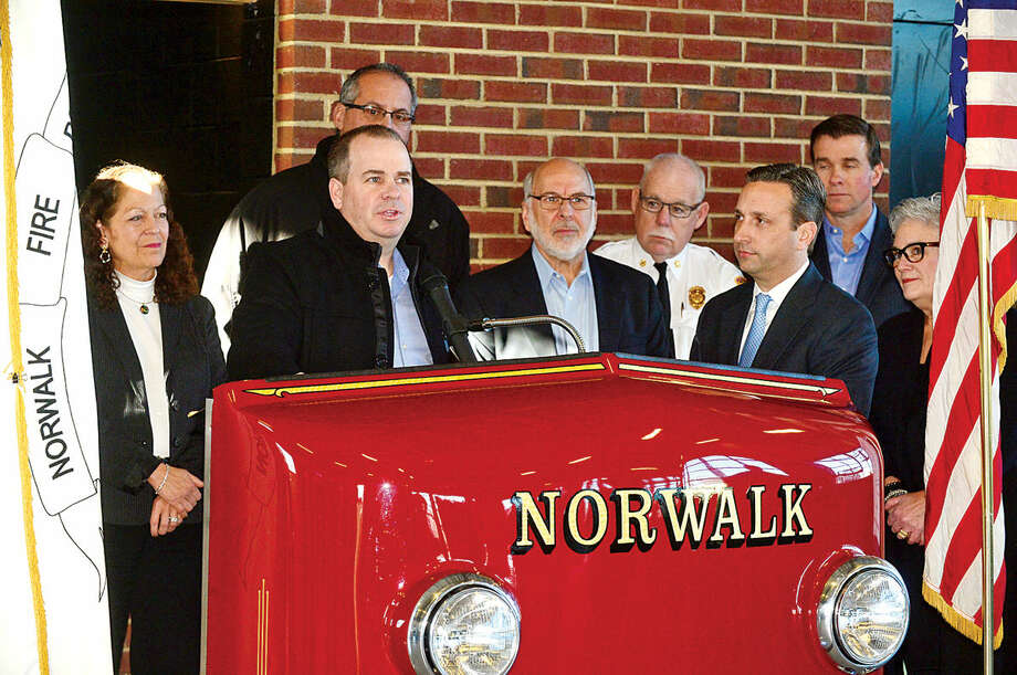 Hour photo / Erik Trautmann Matt Hefferan of the Norwalk Police Activities League thanks State Senator and Majority Leader, Bob Duff (D-25), as the senator holds a press conference Thursday morning at the Norwalk Fire Department to present checks to various organizations from his annual fundraising effort, The Duff's Community Holiday Open House.