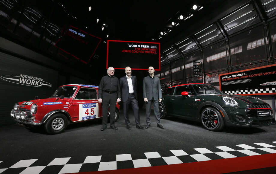 Rauno Aaltonen, from left, winner of the 1967 Rallye Monte Carlos; Jochen Goller, Senior Vice President, Mini; and David Duncan, Vice President, Mini of the Americas pose with a newly unveiled John Cooper Works hardtop, right, and a 1965 Mini Cooper S rally car, left, at media previews for the North American International Auto Show in Detroit Monday, Jan. 12, 2015. (AP Photo/Paul Sancya)