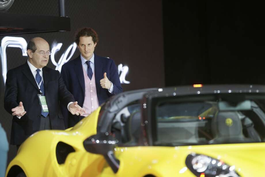 Fiat design chief Lorenzo Ramaciotti, left, and Chairman of Fiat Chrysler Automobiles John Elkann look over the Alfa Romeo 4C Spider during the North American International Auto Show, Monday, Jan. 12, 2015 in Detroit. (AP Photo/Carlos Osorio)