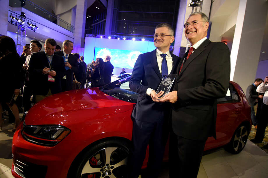 Volkswagen US CEO Michael Horn, left, and board member Dr. Heinz-Jakob Neuser accept the North American Car of the Year Award next to the winning Volkswagen Golf at the North American International Auto Show, Monday, Jan. 12, 2015, in Detroit. (AP Photo/The Grand Rapids Press, Tanya Moutzalia)