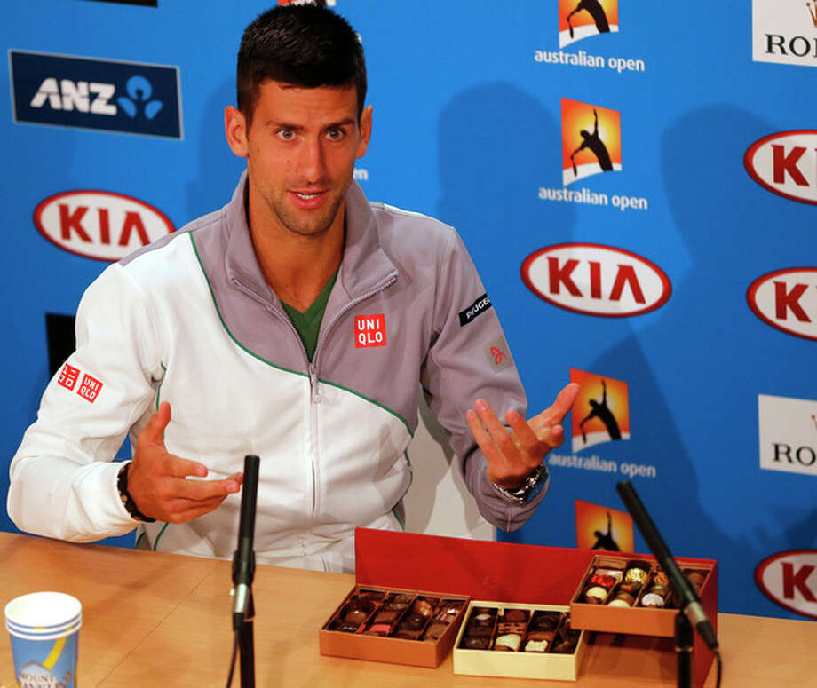 Novak Djokovic of Serbia sits next to boxes of chocolate before handing out reporters during a press conference, ahead of the Australian Open tennis championship in Melbourne, Australia, Sunday, Jan. 12, 2014. (AP Photo/Shuji Kajiyama) / AP