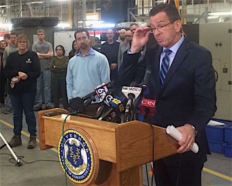 Gov. Dannel P. Malloy takes questions about GE at a hastily arranged appearance at Pegasus Manufacturing in Middletown. At left is the company president, Chris DiPentima.