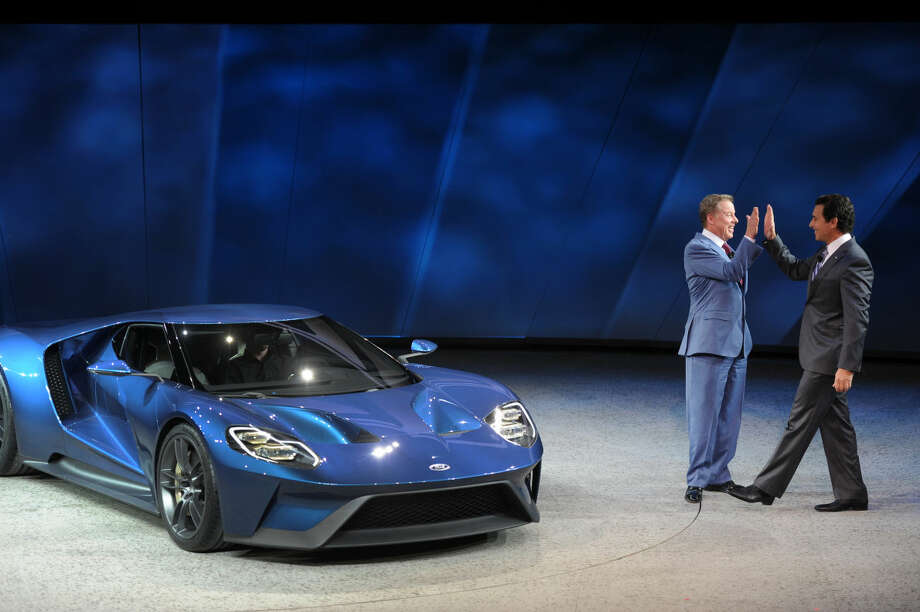 Ford Executive Chairman Bill Ford, left, and CEO Mark Fields high five after unveiling the Ford GT, a super car that will go into production next year, at the North American International Auto Show in a special unveiling inside Joe Louis Arena Downtown Detroit Monday Jan. 12, 2015. (AP Photo/The Grand Rapids Press, Tanya Moutzalia)