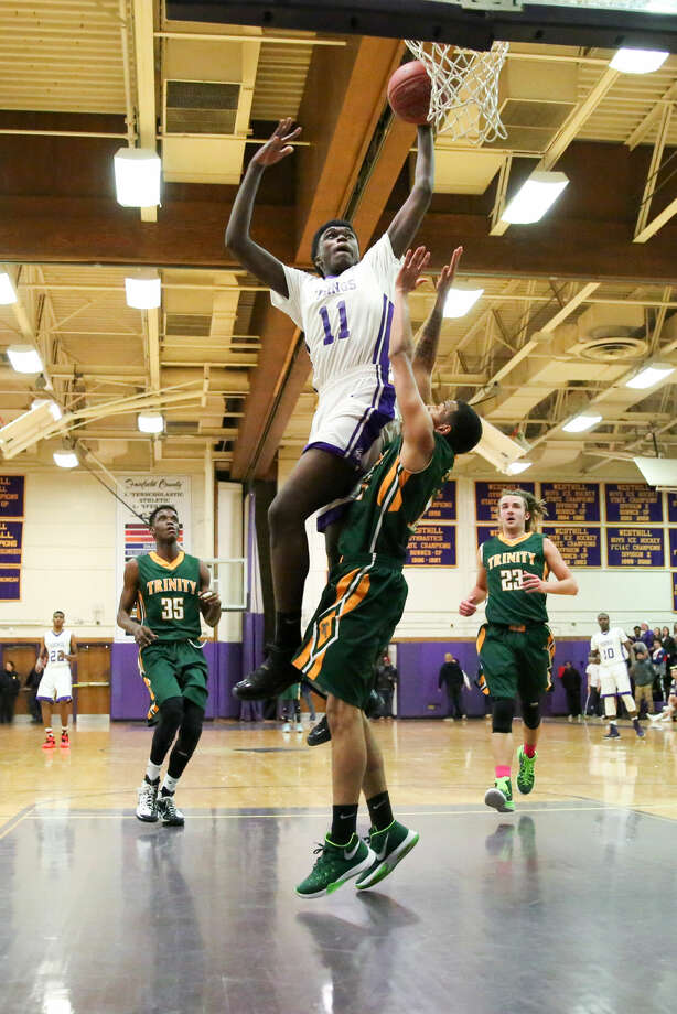 Westhill's Lenold August goes up for a dunk against Trinity Catholic at Westhill High School Tuesday night.