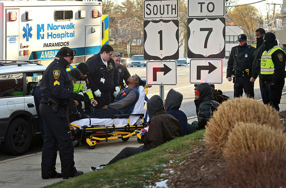 Hour photo / Erik Trautmann Norwalk Paramedics and EMTs transport a young male to Norwalk Hospital after Norwalk police stopped a vehicle on Cross St while investigating an altercation at 41 Wilton Ave. Tuesday afternoon.