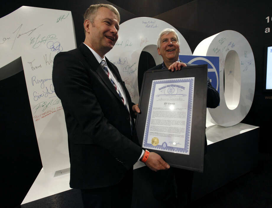 Michigan Gov. Rick Snyder, right, presents ZF CEO Stefan Summer with a special Michigan tribute during the North American International Auto Show Tuesday, Jan. 13, 2015 in Detroit. ZF's North American headquarters are located in Northville, Mich. (AP Photo/Detroit Free Press, Diane Weiss) DETROIT NEWS OUT; NO SALES