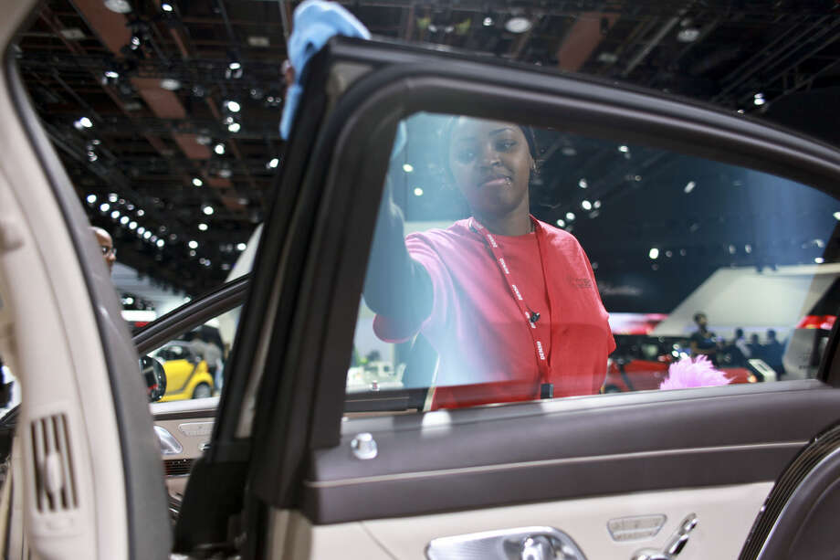 CORRECT BYLINE TO ELAINE CROMIE INSTEAD OF TANYA MOUTZALIAS - Teshawna Parker cleans a Mercedes-Benz before the North American International Auto Show, Monday, Jan. 12, 2015, in Detroit. More than 40 vehicles are expected to be unveiled at the event. (AP Photo/The Grand Rapids Press, Elaine Cromie)