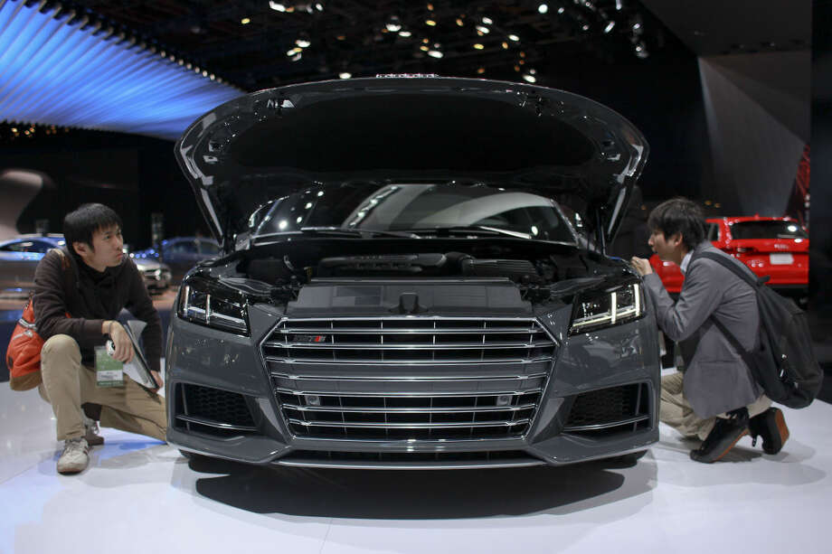 Two men look over the engine of a car during the North American International Auto Show on Tuesday, Jan. 13, 2015 at Cobo Center in Detroit. (AP Photo/The Grand Rapids Press, Elaine Cromie)
