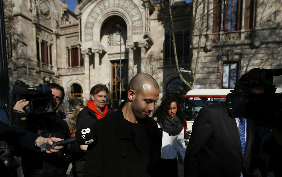 FC Barcelona defender Javier Mascherano, centre, from Argentina, leaves the court after answering questions in a tax fraud case in Barcelona, Spain, Thursday, Jan. 21, 2016. Mascherano has accepted a one-year prison sentence for not properly paying taxes in Spain but is not expected to face any jail time. The sentencing on Thursday came nearly three months after the Barcelona defender had reached a deal with prosecutors and the attorney's office for failing to pay nearly 1.5 million euros ($1.6 million) in taxes for 2011 and 2012. (AP Photo/Manu Fernandez)