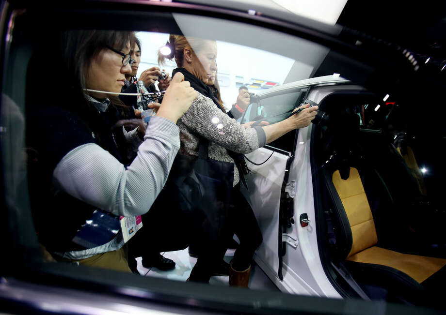 Journalists get a look at the 2016 Cadillac CTS-V after it was introduced at the North American International Auto Show on Tuesday, Jan. 13, 2015, in Detroit. (AP Photo/Detroit Free Press, Regina H. Boone) DETROIT NEWS OUT; NO SALES