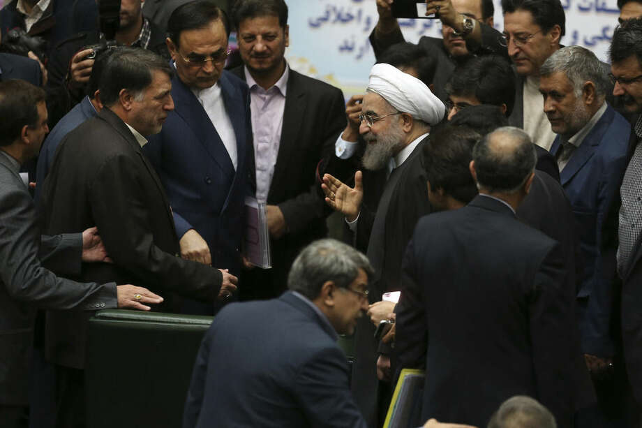 "Iranian President Hassan Rouhani, center, gestures as he is greeted by lawmakers at the parliament to present draft of the country's next year budget and sixth development plan in Tehran, Iran, Sunday, Jan. 17, 2016. Rouhani said Sunday that the official implementation of the landmark deal reached between Tehran and six world powers has satisfied all parties except radical extremists. Rouhani said the deal has ""opened new windows for engagement with the world."" (AP Photo/Vahid Salemi)"