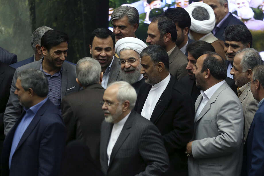 AP Photo/Vahid SalemiIranian President Hassan Rouhani, center, is surrounded by lawmakers as he arrives at the parliament to present a draft of the country's new budget and sixth development plan in Tehran, Iran, Sunday, Jan. 17.