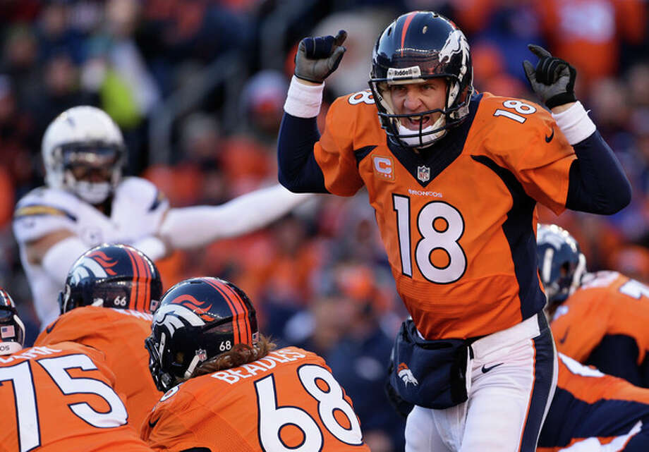 Denver Broncos quarterback Peyton Manning (18) calls an audible at the line of scrimmage against the San Diego Chargers in the first quarter of an NFL AFC division playoff football game, Sunday, Jan. 12, 2014, in Denver. (AP Photo/Charlie Riedel) / AP
