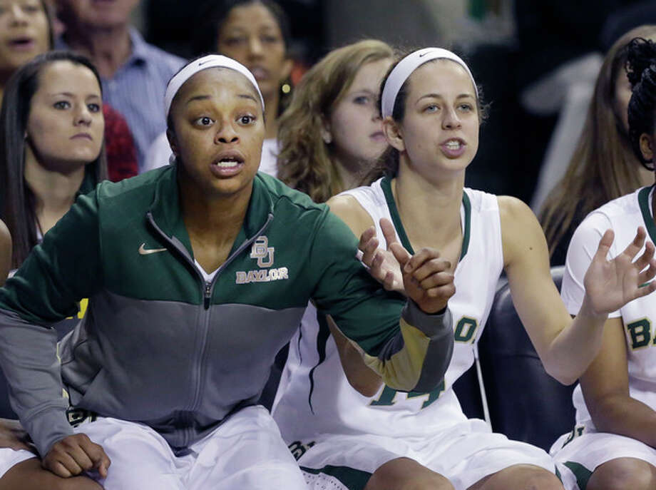 Baylor guard Odyssey Sims, left, and teammate Makenzie Robertson watch from the bench during the second half of an NCAA college basketball game against TCU, Saturday, Jan. 11, 2014, in Waco, Texas. Baylor won 80-46. (AP Photo/LM Otero) / AP