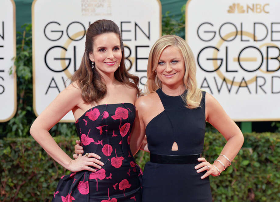 Tina Fey, left, and Amy Poehler arrive at the 71st annual Golden Globe Awards at the Beverly Hilton Hotel on Sunday, Jan. 12, 2014, in Beverly Hills, Calif. (Photo by John Shearer/Invision/AP) / Invision