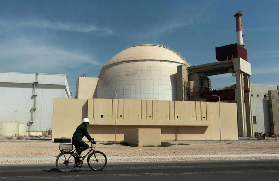 FILE - In this Oct. 26, 2010 file photo, a worker rides a bicycle in front of the reactor building of the Bushehr nuclear power plant, just outside the southern city of Bushehr. Iran and six world powers have agreed on how to implement a nuclear deal struck in November, with its terms starting from Jan. 20, officials announced Sunday. (AP Photo/Mehr News Agency, Majid Asgaripour, File) / AP