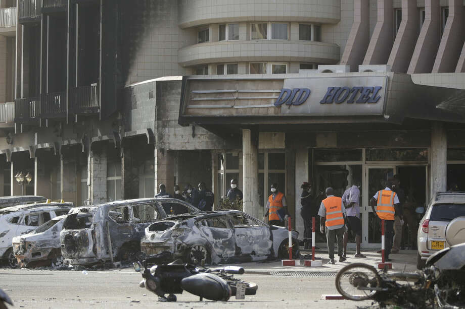Rescue workers inspect damaged cars at the entrance of the Splendid Hotel in Ouagadougou, Burkina Faso, Saturday, Jan. 16, 2016. The overnight seizure of a luxury hotel in Burkina Faso's capital by al-Qaida-linked extremists ended Saturday when Burkina Faso and French security forces killed four jihadist attackers and freed more than 126 people, the West African nation's president said. (AP Photo/Sunday Alamba)