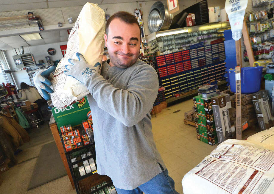 Hour photo/Alex von Kleydorff Kevin McCormack lifts a bag of ice melt to bring to a customers car at Carlyn Hardware on Thursday