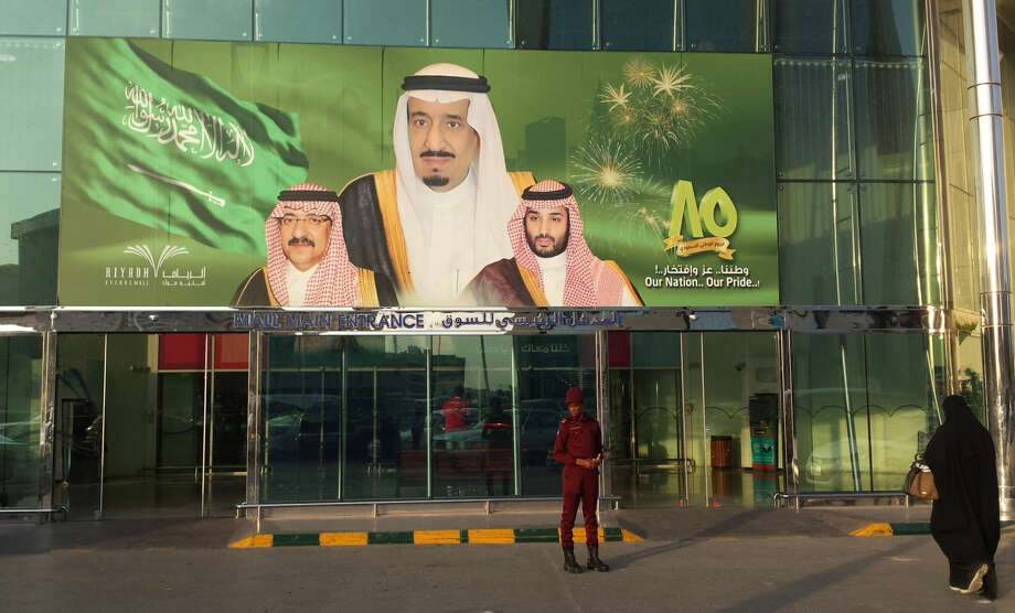 FILE -- In this Dec. 14, 2015 file photo, images of King Salman, center, Crown Prince Mohammed bin Nayef , left, and Deputy Crown Prince Mohammed bin Salman hang at the entrance of a shopping center in Riyadh, Saudi Arabia to mark the country's 85th anniversary. Within hours of ascending to the Saudi throne, King Salman announced sweeping changes that would recast the kingdom's line of succession, and rework its security and economic decision-making processes. It marked the start of what would be a tumultuous year for King Salman, who completes one year as monarch on Saturday, Jan. 23, 2016. (AP Photo/Aya Batrawy, File)