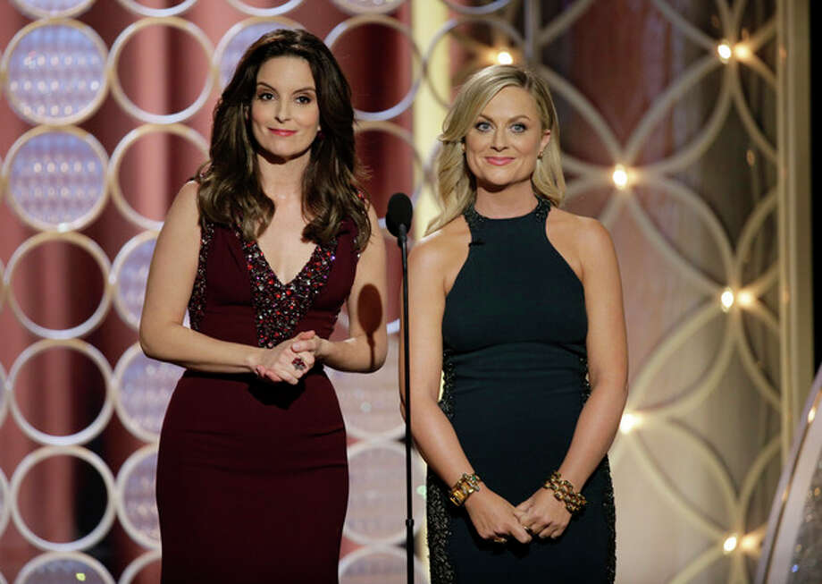 This image released by NBC shows hosts Tina Fey, left, and Amy Poehler during the 71st annual Golden Globe Awards at the Beverly Hilton Hotel on Sunday, Jan. 12, 2014, in Beverly Hills, Calif. (AP Photo/NBC, Paul Drinkwater) / NBC