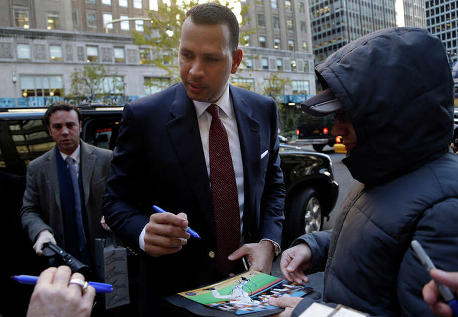 Alex Rodriguez signs autographs as he arrives at Major League Baseball headquarters in New York, Tuesday, Nov. 19, 2013. Rodriguez's grievance hearing to overturn his 211-game suspension resumed Monday with the first of what could be 10 straight days of sessions. (AP Photo/Seth Wenig) / AP