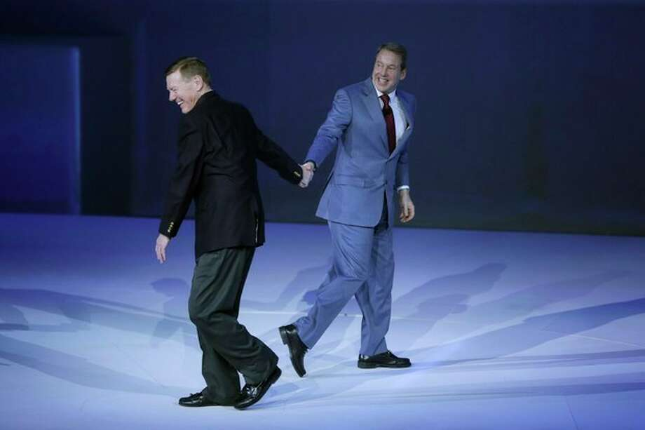 Alan Mulally, president and CEO of the Ford Motor Co., left, walks by executive chairman Bill Ford at the North American International Auto Show in Detroit, Monday, Jan. 13, 2014. (AP Photo/Carlos Osorio) / AP