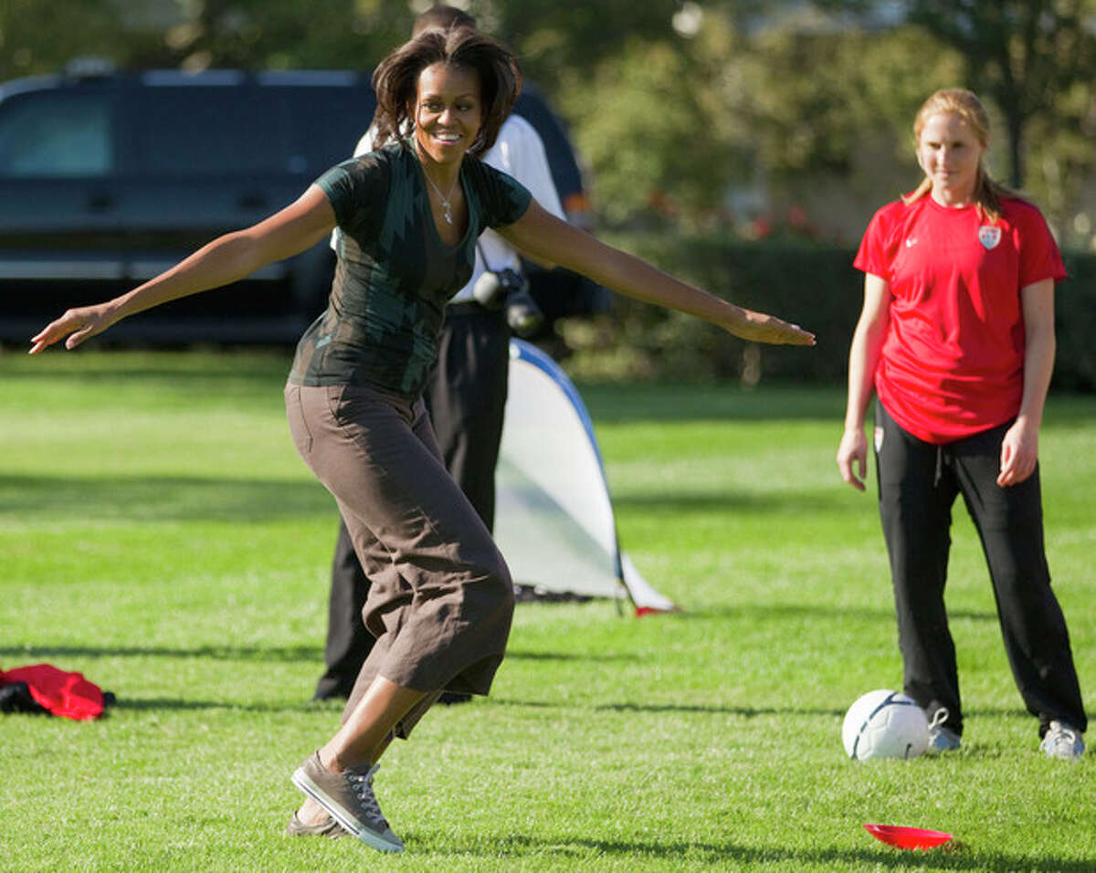 FILE - In this Oct. 6, 2011, file photo, first lady Michelle Obama plays soccer on the South Lawn of the White House in Washington, as part of a Let's Move! clinic. The nation?'s first lady turns 50 on Friday and, by her own account, feels more relaxed now that President Barack Obama?'s days as a candidate for elected office are over. (AP Photo/Evan Vucci)
